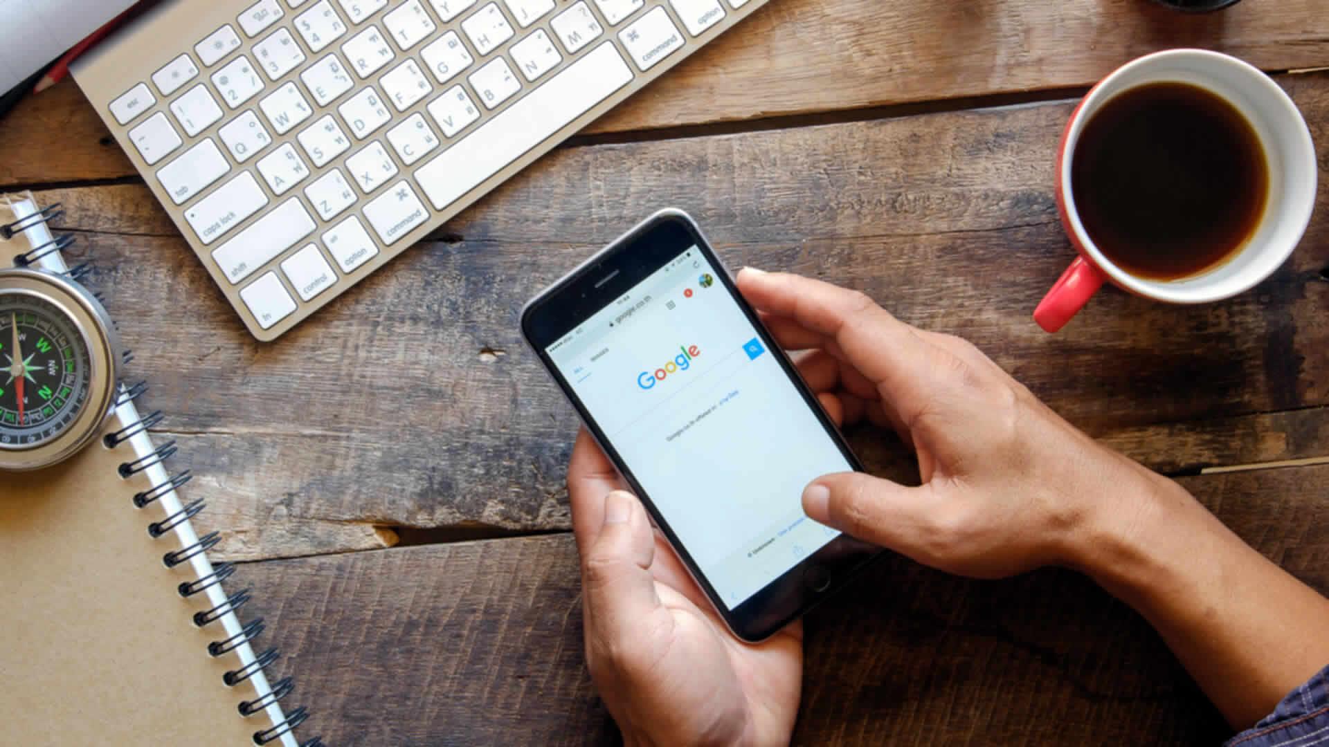 Mãos sobre a mesa segurando um smartphone com o Google na tela. Ao redor, teclado, caderno, bússola e caneca com café.